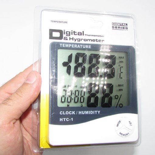 نمای بسته بندی دماسنج دیجیتالی دارای رطوبت سنج و ساعت مدل HTC1 در دست